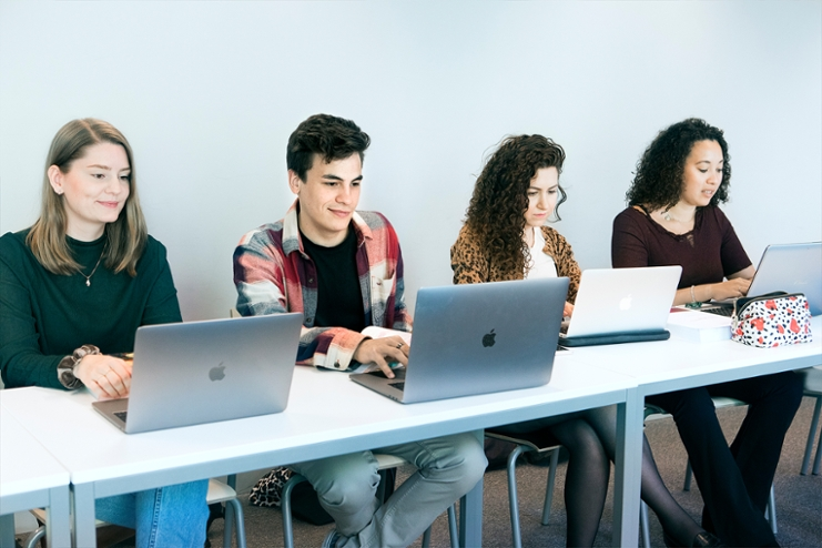 Four law students sitting behind a laptop