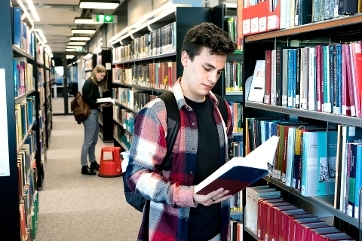 Male law student in legal library taking a book from the shelf