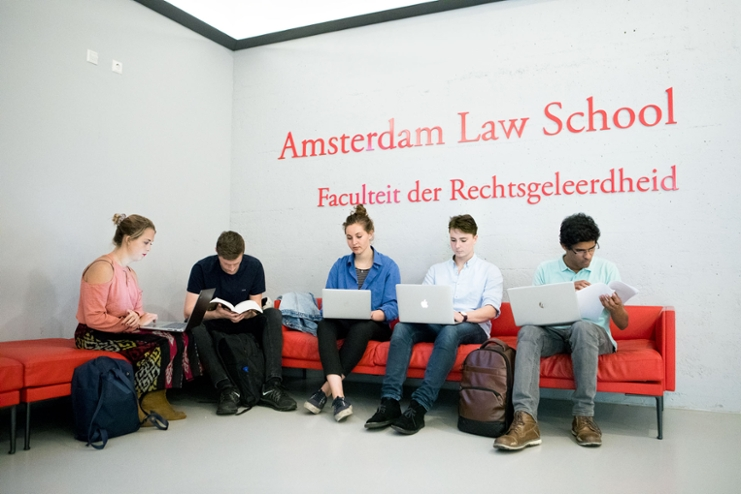 Law students are sitting on red benches under the logo of the Amsterdam Law School