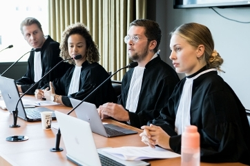 Close-up van rechtenstudenten in toga als rechters in een mootcourt