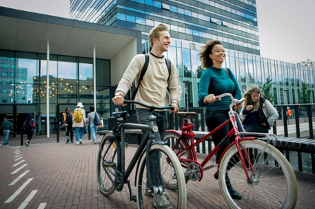 Boy and girl with their bikes on the campus