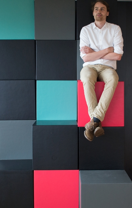 Man sitting on stacked cubes.